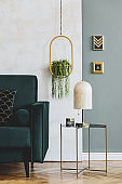 Stylish and luxury interior design of living room with green velvet sofa, design coffee table, marble table lamp, hanging gold flowerbed and elegant accessories. Template. Modern home decor.