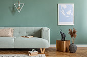 Stylish and scandinavian composition of living room interior with mint sofa, pillow, mock up poster frame, wooden cube, books and elegant accessories. Template. Cozy home decor. Eucalyptus color.