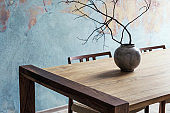 Close up of design wooden table with, stylish chairs, flowers in vase and elegant accessoreis. Details of home decor. Indusrtial concept of dining room. Open space. Template. Old wall.