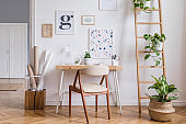 Design scandinavian interior of home office space with stylish chair, wooden desk, ladder, cube, elegant accessories and mock up posters frames. Stylish home decor. Template. White wall.