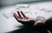 Close up of hands with pills. The person holds back from taking the tablets. Don't take a drugs.