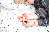 Depressed young blond woman lying in her bed and taking anti-depressant medications. Top view. Mental problems with depression and bulimia.