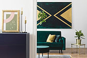 Modern and luxury interior of living room with pomegranate shelf, gold table lamp, mock up poster frame, sofa, plant and elegant accessories. Design paintings on the wall. Stylish home decor. Template