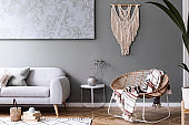 Modern boho interior design of sitting room with design rattan armchair, gray sofa, coffee table, beige macrame, plants and elegant accessories. Stylish home decor. Abstract paintings. Template.