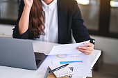 Businesswoman using and working on laptop computer and paperwork