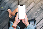 a woman holding a black mobile phone with blank white desktop screen