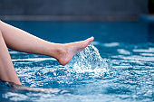 legs and left foot kicking and splashing water in the pool