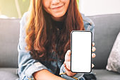 a beautiful woman holding and showing black mobile phone with blank screen in cafe