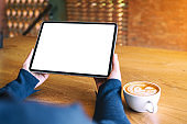a woman holding black tablet pc with blank white screen with coffee cup on wooden table