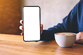 a woman holding and showing black mobile phone with blank white screen while drinking coffee