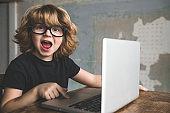 Little boy having fun using laptop