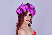 woman portrait with bright artistic makeup floral crown flowers magenta pink orchid flowers looking at you camera
