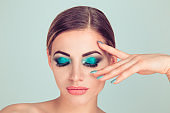 woman fashion model girl blue green makeup eye shadow looking down showing nails manicure color in set with eyeshadows