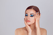 woman with closed eyes posing showing perfect blue green eye shadows