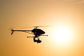 Helicopter camera drone silhouetted against the late afternoon sun