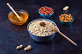 Dry oatmeal, nuts and honey. Oatmeal and migdal nuts on dark background. Cereal and peanuts for making healthy breakfast. Vegetarian food