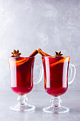 Two glasses of mulled wine with spices on cement background. Christmas mulled wine with orange, star anise and cinnamon. Red mulled wine on a gray background. Minimalism. Copy space