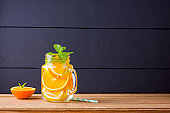 Infused water with orange, lemon and mint. Mug delicious refreshing drink of mix fruits with mint on wooden boards. Iced summer drink in mason jar. Homemade detox cocktail