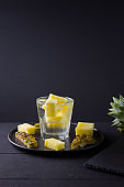 Pineapple on a dark background. Sliced pineapple on a black plate. Drink with ice and pineapple slices. Infused water. Copy space