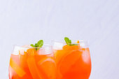 Aperol Spritz cocktail with mint leaves on a white background. A glass of summer alcohol cocktail with orange slices. Classic Italian drink coral color