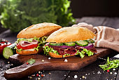 Fresh burgers on wooden table and dark background