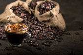 Coffee cup and sacks with coffee beans on a black table.