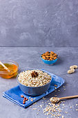 Dry oatmeal, nuts and honey. Oatmeal and almond nuts on cement background. Cereal and peanuts for healthy breakfast. Oatmeal in bowl on blue napkin