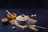 Dry oatmeal, nuts and honey. Oatmeal and almond nuts on dark background. Cereal and peanuts for making healthy breakfast. Oatmeal on burlap
