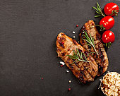 Grilled pork steak with tomato, pepper, rosemary and spices on black background