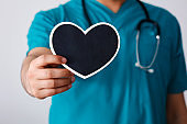 Doctor holds a small black heart shape