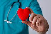 Doctor holds a small red heart shape