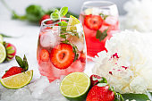 Pink lemonade with strawberries, lime, basil and mint