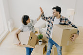 New home. Happy woman and man celebrate moving to new apartment, pose in empty room with cardboard boxes and couch in background, give each other high five. People, home, real estate concept
