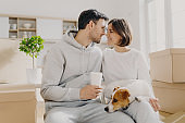 Photo of lovely woman and man going to kiss, husband holds takeaway coffee, sit indoor near cardboard boxes, unpack personal belongings on relocating day, live with pet, buy new expensive flat
