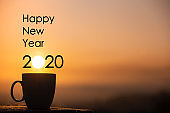 Silhouette coffee cup with happy new year 2020 text on a sunrise background