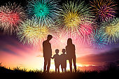 happy family standing and watching the fireworks