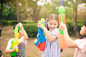 happy children playing with water guns on summer