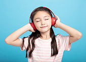 happy little girl with headphones listening to music