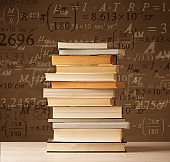 Books on vintage background with math formulas