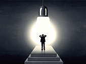 Man standing on a step in front of a huge light bulb