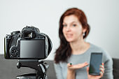 A young beautiful girl is sitting in front of a DSLR and recording a Vlog, close-up. Blogger, blogging, technology, online money, online courses. copy space.