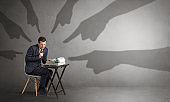 Shadow hands pointing at a small worker