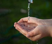 boy washes his hand under the faucet in garden