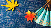 Autumn of Japanese maple and maple wasabi. With margins A bird's-eye view of a light blue-green fan placed on a Japanese fabric with a blue background.