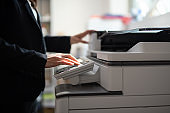 Businesswoman making copies with copy machine at office