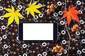 Japanese-style autumn of the wasabi of the dead branch of a smart phone, maple and maple. The angle is a bird's-eye view and is placed on a dark brown Japanese-style cloth.