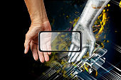 5G future image created by humans and AI robots. A newly born 5th generation mobile communication system smartphone placed on the palm of a metallic robot and the palm of a human being. The background is an abstract image of outer space and electronic cir