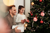 Girl and her daddy decorating Christmas tree