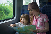 Mother and child reading map while travelling by train