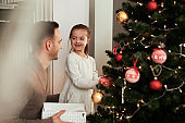 Girl and daddy decorating the Christmas tree